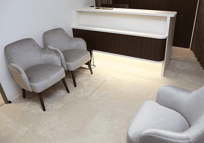 クリニックの受付・待合室の様子です。カウンターと椅子が並んでいます
