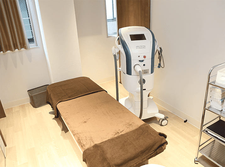 クリニックの施術室の画像です。診療ベッドと美容器具が置いてあります。