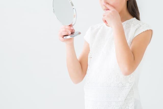 女性が鼻にできた稗粒腫を鏡で確認している