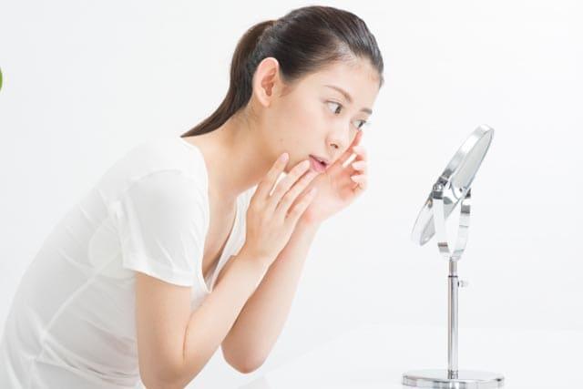 20代の女性が顔にできた稗粒腫を鏡でチェックしている